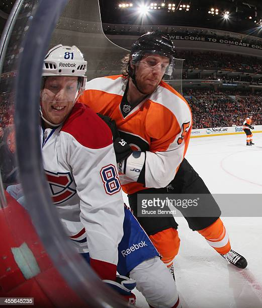 Lars Eller of the Montreal Canadiens is hit into the boards by Braydon Coburn of the Philadelphia Flyers during the first period at the Wells Fargo...