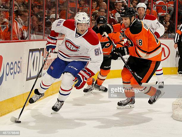 Lars Eller of the Montreal Canadiens takes the puck as RJ Umberger of the Philadelphia Flyers defends on October 11 2014 at the Wells Fargo Center in...