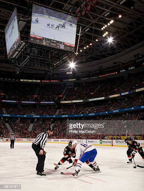 Lars Eller of the Montreal Canadiens wins a faceoff against Jason Spezza of the Ottawa Senators with the new HD Videoboard mounted in the background...