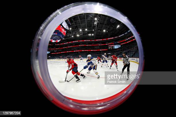 Lars Eller of the Washington Capitals skates past Henri Jokiharju of the Buffalo Sabres during the second period at Capital One Arena on January 22,...