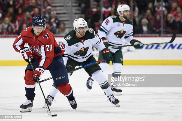 Lars Eller of the Washington Capitals skates with the puck against Matt Read of the Minnesota Wild in the third period at Capital One Arena on March...