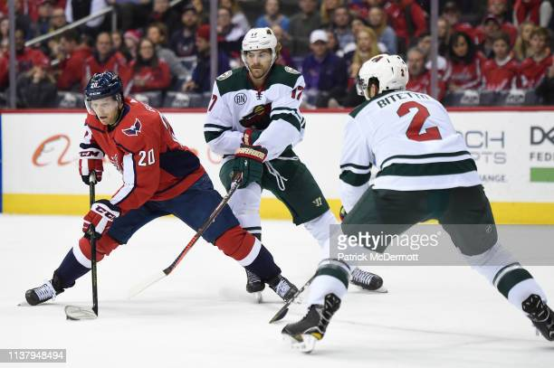 Lars Eller of the Washington Capitals skates with the puck against Marcus Foligno of the Minnesota Wild in the third period at Capital One Arena on...