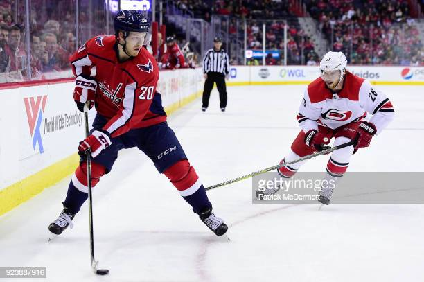Lars Eller of the Washington Capitals skates with the puck against Elias Lindholm of the Carolina Hurricanes in the first period at Capital One Arena...