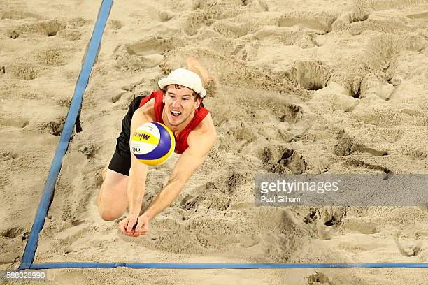 Lars Fluggen of Germany digs the ball in the corner of the court against Nikita Liamin and Dmitr Barsuk of Russia during the Beach Volleyball Women's...