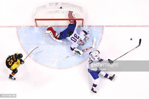 Lars Haugen and Alexander Bonsaksen of Norway make a save against Felix Schutz of Germany in the second period during the Men's Ice Hockey...