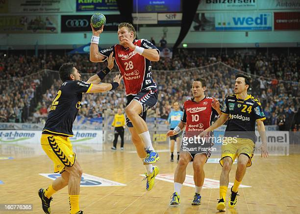 Lars Kaufmann of Flensburg challenges for the ball with Alexander Petersson of RheinNeckar during the DHB cup game between SG Flensburg Handewitt and...