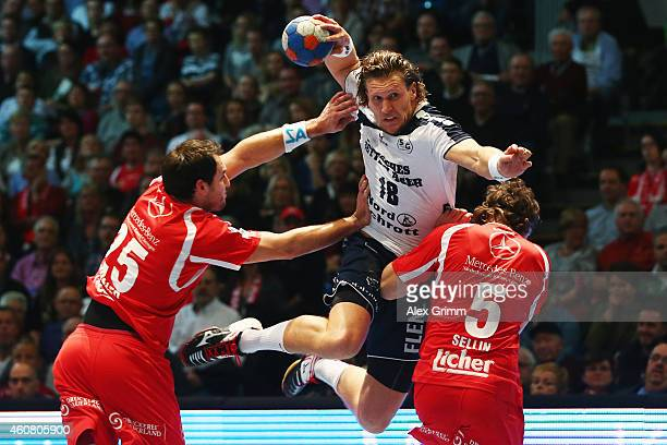 Lars Kaufmann of FlensburgHandewitt is challenged by Michael Mueller and Johannes Sellin of Melsungen during the DKB Handball Bundesliga match...