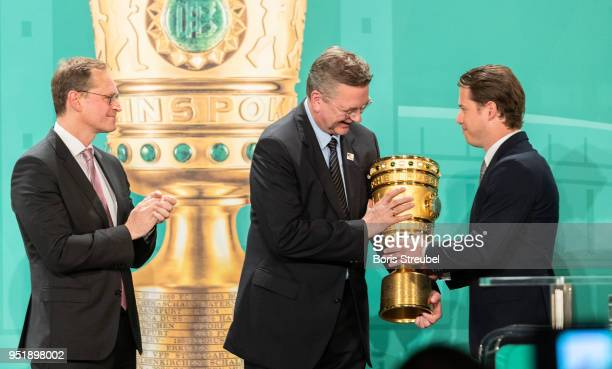 Lars Ricken representative of Borussia Dortmund hands the cup over to Reinhard Grindel president of the German Football Association during the DFB...