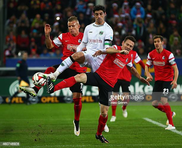 Lars Stindl hh is challenged by Jonathan Schmid and Sascha Riether of Freiburg during the Bundesliga match between SC Freiburg and Hannover 96 at...