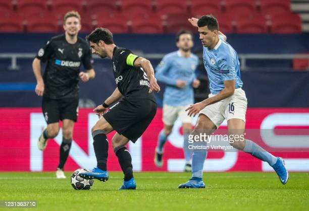 Lars Stindl of Borussia Moenchengladbach in action with Rodri of Manchester City during the UEFA Champions League Round Of 16 Leg One match between...