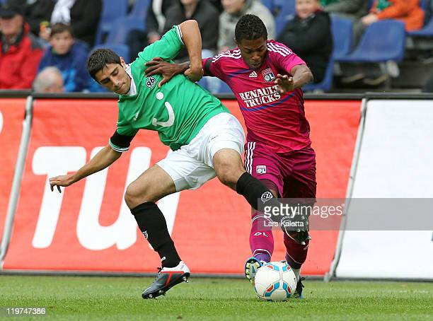 Lars Stindl of Hannover96 challenges for the ball with Michel Fernandez Bastos of Lyon during the pre season friendly match between Hannover 96 and...