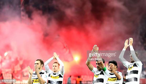 Lars Stindl of Moenchengladbach and his team mates go to their fans while fans of Leverkusen burn flares during the Bundesliga match between Bayer 04...