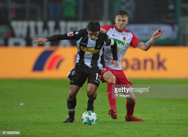 Lars Stindl of Moenchengladbach and Jeffrey Gouweleeuw of Augsburg battle for the ball during the Bundesliga match between Borussia Moenchengladbach...