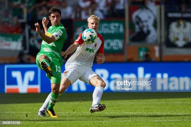 Lars Stindl of Moenchengladbach and Martin Hinteregger of Augsburg battle for the ball during a Bundesliga match between FC Augsburg and Borussia...
