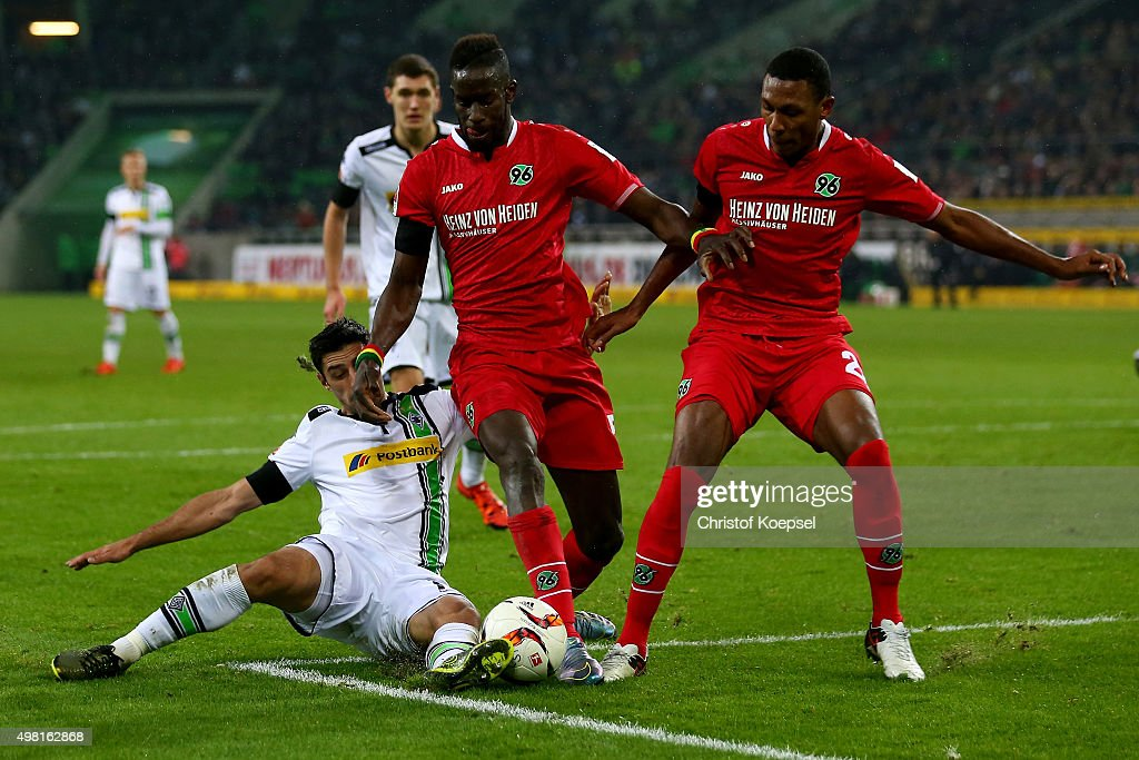 Lars Stindl of Moenchengladbach challenges Salif Sane (C) and Marcelo of Hannover during the Bundesliga match between Borussia Moenchengladbach and Hannover 96 at Borussia-Park on November 21, 2015 in Moenchengladbach, Germany.