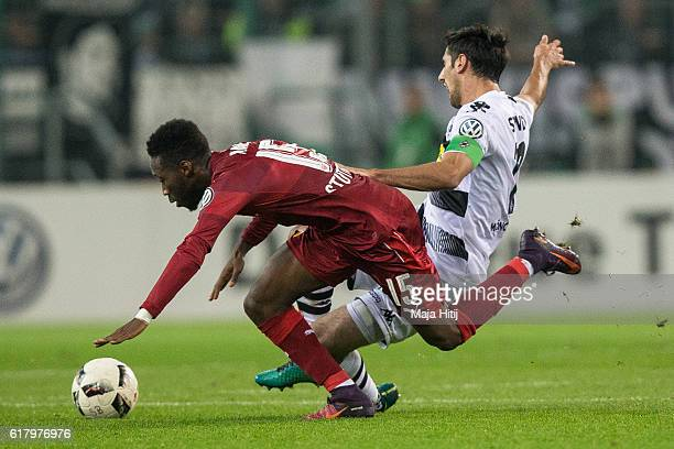 Lars Stindl of Moenchengladbach is challenged by Carlos Mane of Stuttgart during the DFB Cup match between Borussia Moenchengladbach and VfB...