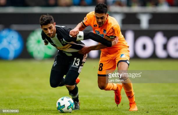 Lars Stindl of Moenchengladbach is challenged by Nadiem Amiri of Hoffenheim during the Bundesliga match between Borussia Moenchengladbach and TSG...