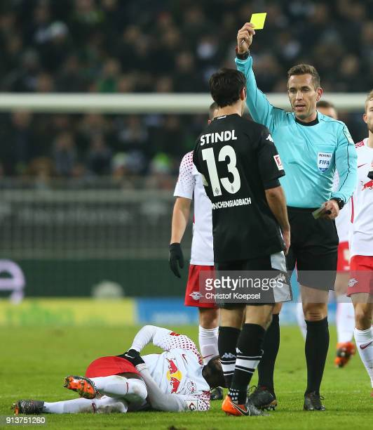 Lars Stindl of Moenchengladbach is shown a yellow card by referee Tobias Stieler during the Bundesliga match between Borussia Moenchengladbach and RB...