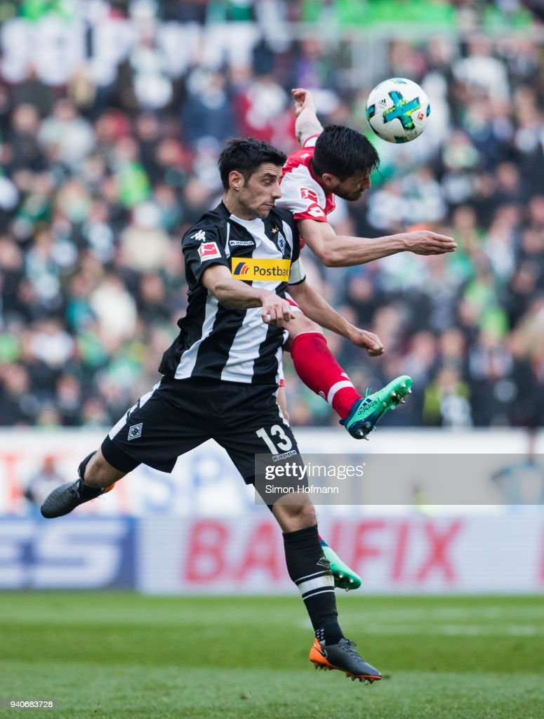 Lars Stindl of Moenchengladbach jumps for a header with Danny Latza of Mainz during the Bundesliga match between 1. FSV Mainz 05 and Borussia Moenchengladbach at Opel Arena on April 1, 2018 in Mainz, Germany.