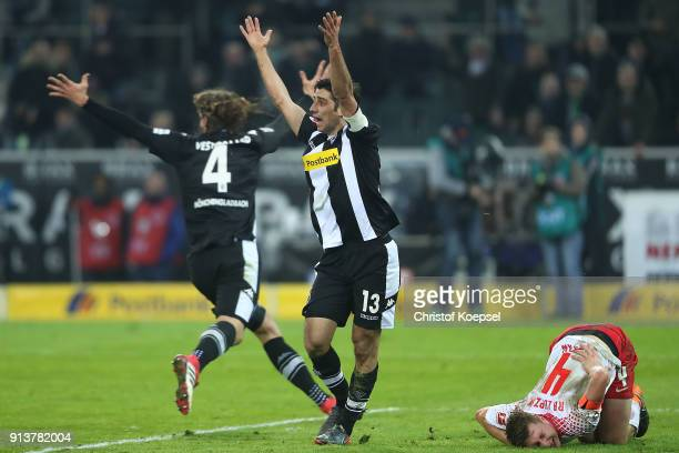 Lars Stindl of Moenchengladbach raises his arms questioning a handball as Willi Orban of Leipzig lies on the pitch in pain and Jannik Vestergaard of...