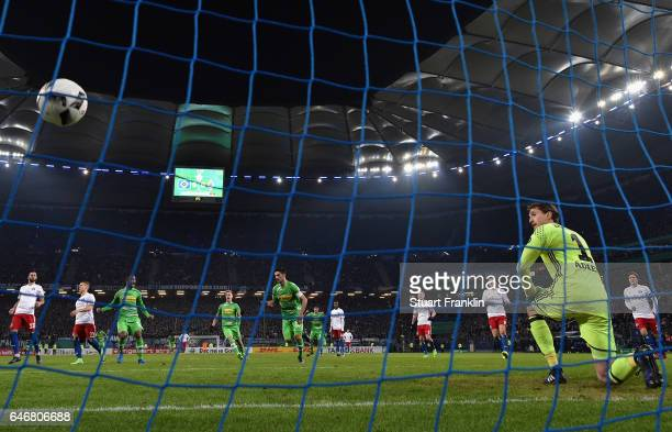 Lars Stindl of Moenchengladbach scores his team's first goal past goalkeeper Rene Adler of Hamburg during the DFB Cup quarter final between Hamburger...