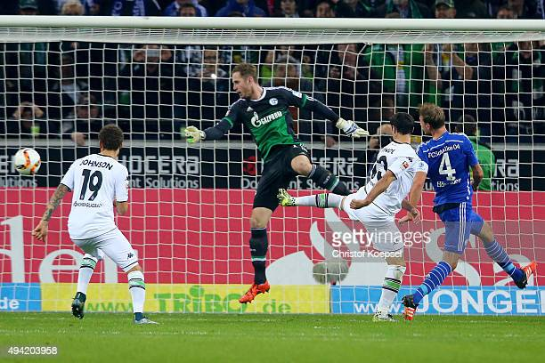 Lars Stindl of Moenchengladbach scores the first goal after a second try of penalty against Ralf Faehrmann of Schalke and Benedikt Hoewedes of...
