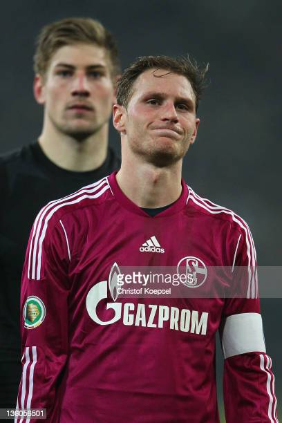 Lars Unnerstall and Benedikt Hoewedes of Schalke look dejected after losing the DFB Cup round of sixteen match between Borussia Moenchengladbach and...