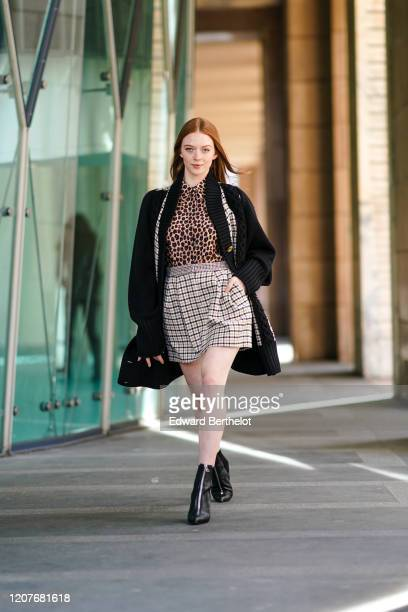 Larsen Thompson a black oversized wool jacket, a brown leopard print shirt, a checked skirt, black shiny pointy boots, outside Vivetta, during Milan...