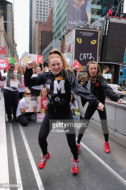 Larsen Thompson and Taylor Hatala dance on top of the 2016 Global Goals Girls Bus in Times Square on September 20 2016 in New York City