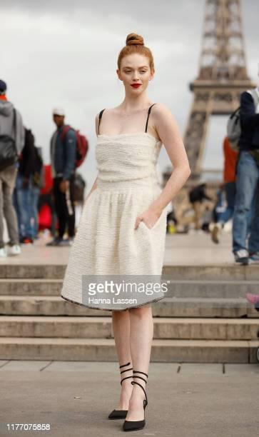 Larsen Thompson wearing a white dress and black strap stilettos outside Rochas on September 25, 2019 in Paris, France.