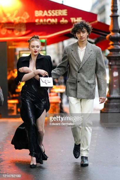 Larsen Thompson wears a balck jacket, a bag, a black silky lustrous flowing skirt, black shoes ; Gavin Casalegno wears a gray blazer jacket, white...