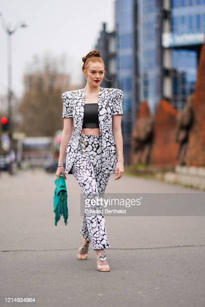 Larsen Thompson wears a black cropped top, a black and white jacket with printed cow patterns and shoulder pads, pants with golden buttons, a green...