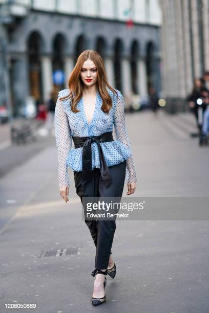 Larsen Thompson wears a blue low-neck mesh ruffled top, a belt, black pants, pointy shoes, outside Philosophy, during Milan Fashion Week Fall/Winter...