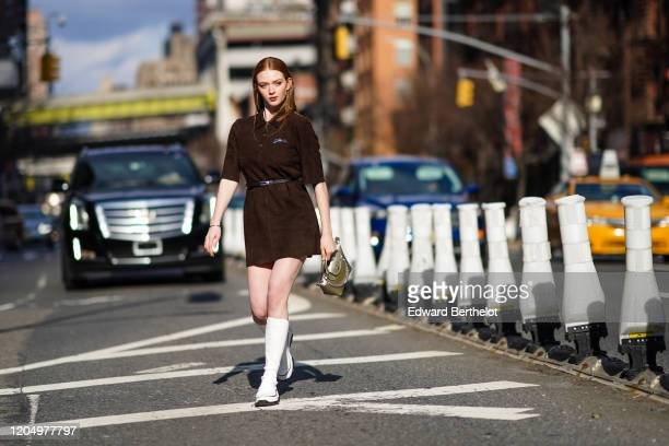Larsen Thompson wears a brown dress a belt a bag with a silver chain white boots outside Longchamp during New York Fashion Week FallWinter 2020 on...