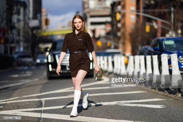 Larsen Thompson wears a brown dress, a belt, a bag with a silver chain, white boots, outside Longchamp, during New York Fashion Week Fall-Winter...