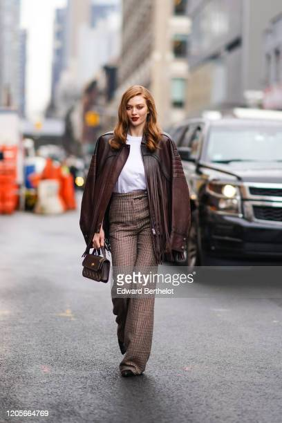 Larsen Thompson wears a brown fringed leather jacket a white tshirt houndstooth pattern printed flared pants a bag outside Coach during New York...