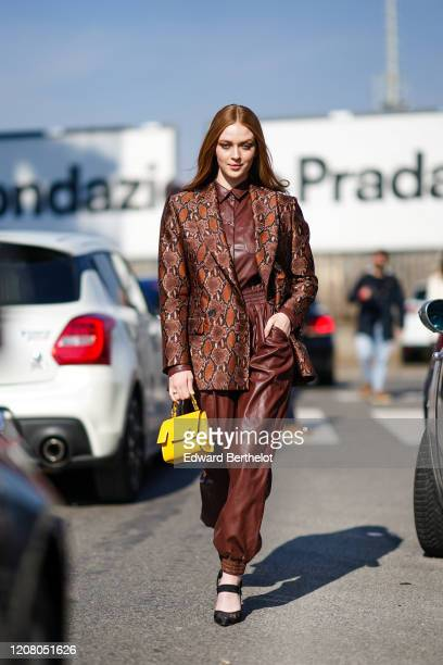 Larsen Thompson wears a brown snake print oversized jacket, a brown leather jumpsuit, outside MSGM, during Milan Fashion Week Fall/Winter 2020-2021...