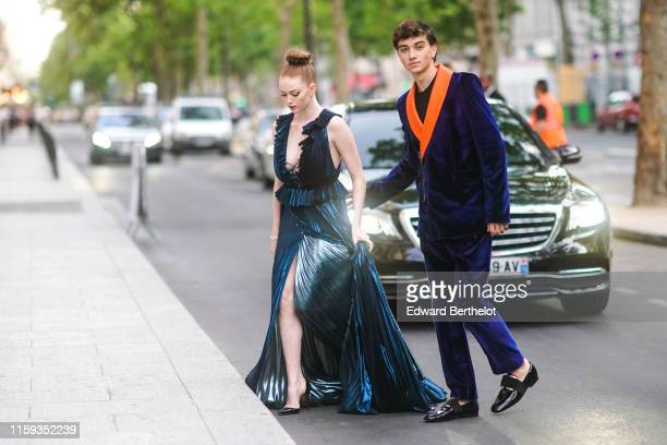 Larsen Thompson wears a shiny deep petrol-blue plunging neckline and side-slit pleated peplum long dress ; Gavin Casalegno wears a black top, a...