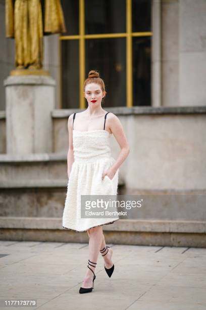 Larsen Thompson wears a white wool gathered dress with black straps black suede pointy anklestrap heels outside Rochas during Paris Fashion Week...