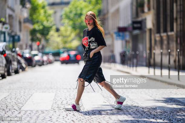 Larsen Thompson wears sunglasses a tshirt with printed road sign black leather shorts Roger Vivier white and purple sneakers during Paris Fashion...
