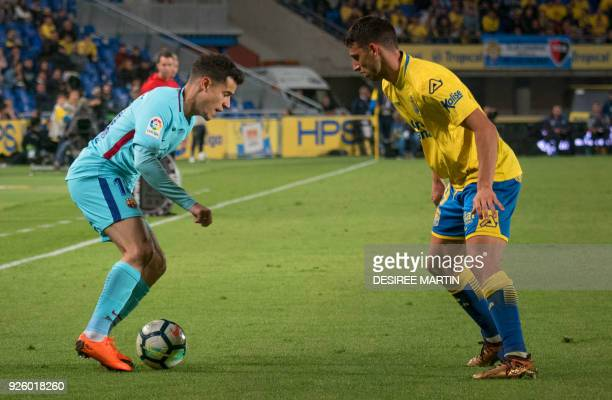 Las Palmas' Argentinian forward Jonathan Calleri vies with Barcelona's Brazilian midfielder Philippe Coutinho during the Spanish league football...