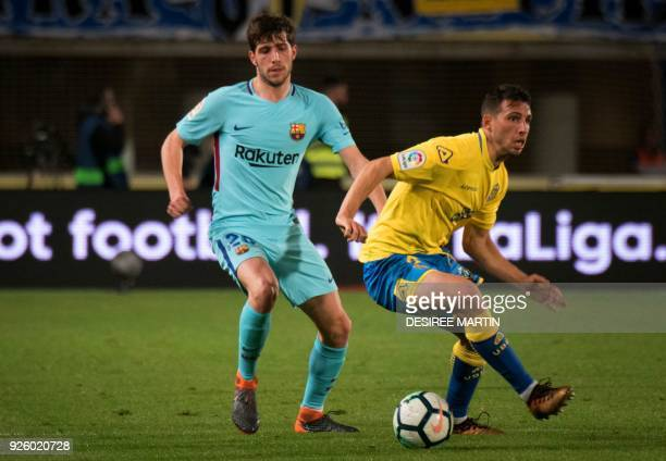 Las Palmas' Argentinian forward Jonathan Calleri vies with Barcelona's Spanish midfielder Sergi Roberto during the Spanish league football match UD...