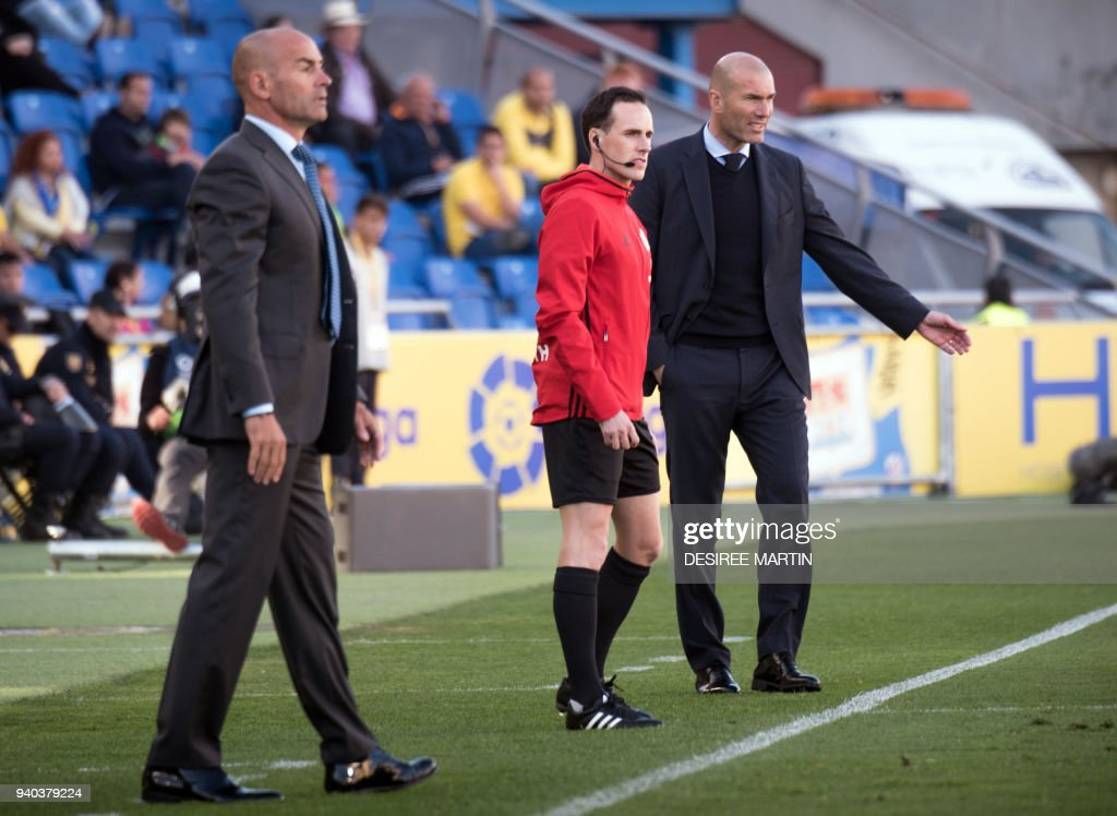 Las Palmas' coach Paco Jemez (L) and Real Madrid's French coach Zinedine Zidane (R) stand on the sideline during the Spanish League football match between UD Las Palmas and Real Madrid CF at the Gran Canaria stadium in Las Palmas on March 31, 2018. /