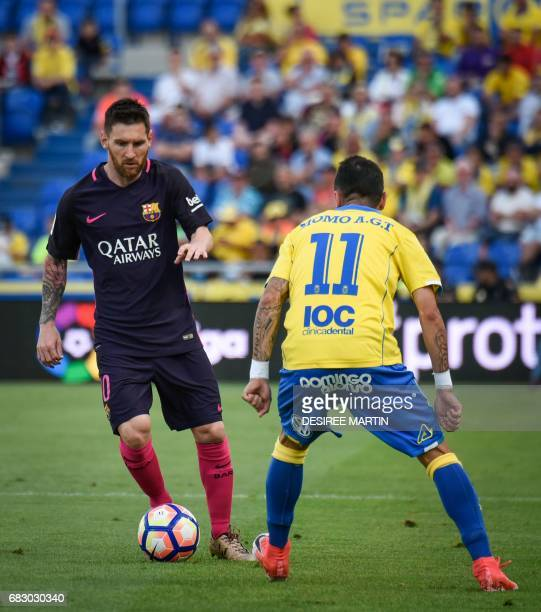 Las Palmas' midfielder Momo vies Barcelona's Argentinian forward Lionel Messi during the Spanish league football match UD Las Palmas vs FC Barcelona...