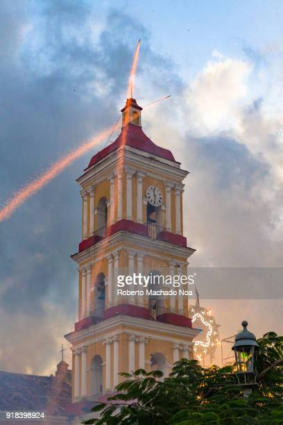 'Las Parrandas' or Christmas Festival Fireworks or firecrackers in the sky in front of the clock and bell tower of the main Catholic Church named...