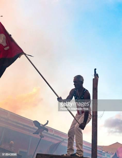 'Las Parrandas' or Christmas Festival man with a USA shirt waving the flag of 'El Carmen' district