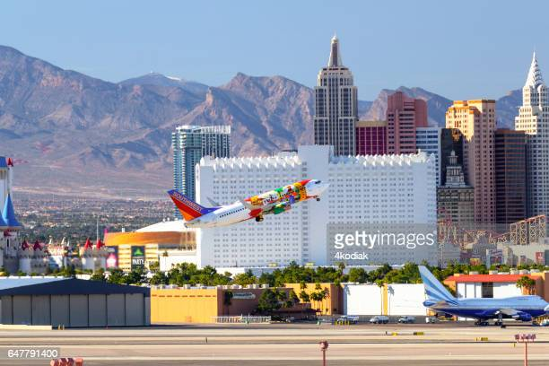 las vegas downtown with airplane taking off. - mccarran international airport stock photos and pictures