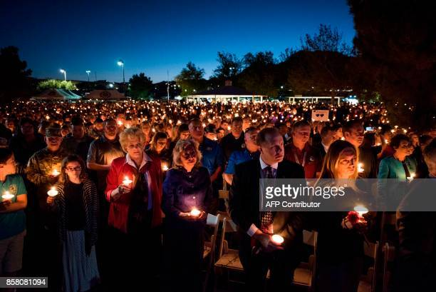 Las Vegas Mayor Carolyn Goodman and thousands of other people hold candles at a memorial service for Charleston Hartfield a Las Vegas police officer...
