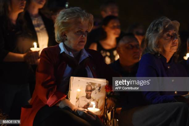 Las Vegas Mayor Carolyn Goodman holds a photo of police officer Charleston Hartfield at his memorial after he was killed on October 1 2017 when a...