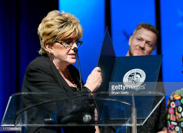 Las Vegas Mayor Carolyn Goodman presents Imagine Dragons a ceremonial proclamation as frontman Dan Reynolds of Imagine Dragons listens during Imagine...